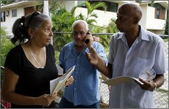 Cuban dissidents Marta Beatriz Roque, left, Vladimiro Roca, center, and Guillermo Farina talk after meeting with journalists in Havana, Tuesday, Aug. 26, 2008. Roque said Tuesday she has filed a criminal complaint against Cuba's communist government for airing on state television evidence it collected by bugging her phone, going through her garbage and secretly filming her. According to Cuba's Constitution, state security agents are allowed to spy on citizens, but it prohibits them from making evidence they collect public.(AP Photo/Javier Galeano)