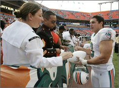 "In this Nov. 11, 2007 file photo, Miami Dolphins kicker Jay Feely, right, autographs a ball for members of the U.S. military after a football game against the Buffalo Bills at Dolphin Stadium in Miami. Apparently unsatisfied with both candidates in a summer-long kicking competition, the Kansas City Chiefs signed free agent Jay Feely to a one-year contract Monday, Aug. 25, 2008. Feely will join Connor Barth and Nick Novak on Tuesday in what coach Herm Edwards called a ""kick-off,"" and one of the three will be released before Thursday night's preseason finale against St. Louis. (AP Photo/Lynne Sladky, File)"