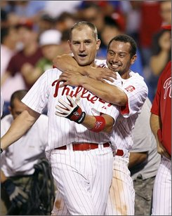 Philadelphia Phillies' Chris Coste gets hugged from behind by Shane Victorino, right, after the Phillies defeated the New York Mets 8-7 in the 13th inning of a baseball game, Wednesday, Aug. 27, 2008, in Philadelphia. Victorino scored the winning run off of Coste's bases-loaded, RBI-single. (AP Photo/Tom Mihalek)