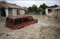 A truck is trapped in mud caused by heavy rain brought by Tropical Storm Gustav in Fond Parisien village in Haiti, Thursday, Aug. 28, 2008.  Gustav moved away from the island of Hispaniola, where it killed 23 people in Haiti and the Dominican Republic, and inched toward Jamaica's low-lying capital, 80 miles (130 kilometers) to the west. Forecasters predicted it would hug Jamaica's southern shore before making a near-direct hit on Grand Cayman. (AP Photo/Ariana Cubillos)