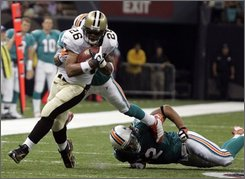 New Orleans Saints running back Deuce McAllister (26) runs past Miami Dolphins linebacker Channing Crowder (52) in the first half of an NFL preseason football game in New Orleans on Thursday, Aug. 28, 2008. (AP Photo/Steve Kashishian)