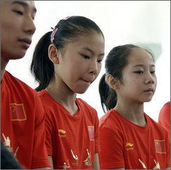 Chinese gymnast He Kexin, center, is seen with teammates at a news conference at the Samsung Pavilion at the 2008 Beijing Olympics in Beijing, Friday, Aug. 22, 2008. Coach Lu Shanzhen told The Associated Press they gave the FIG new documents on Thursday to try to remove any doubts about He Kexin's age, including an old passport, residency card and her current ID card. (AP Photo/Rob Carr)