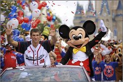 """In this image released by Disney, Olympic goldmedalist Michael Phelps waves to the crowd, Friday, Aug. 29, 2008, during a parade at the Magic Kingdom in Lake Buena Vista, Fla. Phelps, who took home a record-breaking eight gold medals from the Beijing Games, rode through the Magic Kingdom with Mickey Mouse on Friday as part of the """"America's Homecoming Parade"""" at the park.  (AP Photo/Disney, Kent Phillips)"""