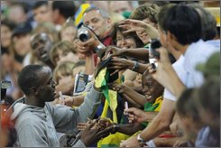 Jamaican Usain Bolt writes autographs after winning the men's 100 m race at the Weltklasse Golden League athletics meeting in the Letzigrund stadium in Zurich, Switzerland, Friday, Friday, Aug. 29, 2008. (AP Photo/Keystone, Eddy Risch)