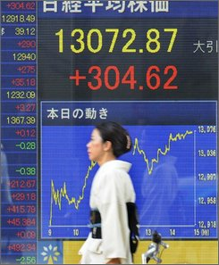  A woman in kimono walks past a Tokyo brokerage's electric stock price board as Japan's benchmark Nikkei stock average surged 304.62 points to close at 13,072.87 Friday, Aug. 29, 2008, marking its biggest one-day percentage gain since Aug. 6. (AP Photo/Katsumi Kasahara)