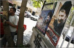 A Lebanese man stands near pictures of top Shiite imam Moussa al-Sadr, right, in Beirut, Lebanon, Friday, Aug. 8, 2008. The country's top Shiite imam vanished during a mystery-shrouded trip to Libya on Aug. 31, 1978. Thirty years later his disappearance remains a burning issue for Lebanon's Shiites, including Hezbollah an indication of his potency as a symbol for a community that has become a major player but still insists it hasn't been given the say it deserves in Lebanon. (AP Photo)
