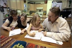 Richard Larson, right, sings a song with his daughter Olivia, 10, center right, as his wife, Marge left, helps their other Beverly, 8, center left, with her homework at their kitchen table in Anchorage, Alaska Thursday Aug. 28, 2008. For the entire Democratic National Convention, speakers have been invoking the kitchen table as the metaphor for the lives of regular Americans. (AP Photo/Al Grillo)