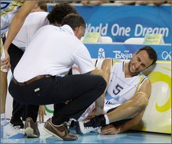 Argenitna's Manu Ginobili of the NBA's San Antonio Spurs grimaces in pain after he injured his ankle during the men's semifinal basketball game agaginst USA at the Beijing 2008 Olympics in Beijing,  Friday, Aug. 22, 2008.  (AP Photo/Dusan Vranic)