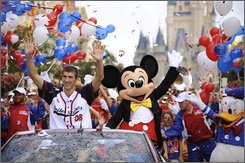 "In this image released by Disney, Olympic gold medalist Michael Phelps waves to the crowd, Friday, Aug. 29, 2008, during a parade at the Magic Kingdom in Lake Buena Vista, Fla. Phelps, who took home a record-breaking eight gold medals from the Beijing 2008 Olympics, rode through the Magic Kingdom with Mickey Mouse on Friday as part of the ""America's Homecoming Parade"" at the park.  (AP Photo/Disney, Kent Phillips)"
