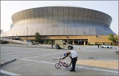 A  young man works on his bicycle in front of the Louisiana Superdome in New Orleans, Saturday, Aug. 30, 2008. The Superdome will not be used as a shelter in the event that Hurricane Gustav reaches New Orleans. (AP Photo/Bill Haber)