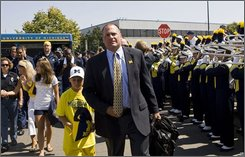 """Michigan head coach Rich Rodriguez, and his son Rhett, lead the football team through a gauntlet of fans to Michigan Stadium, before a college football game agaisnt Utah, Saturday, Aug. 30, 2008, in Ann Arbor, Mich. Michigan calls this a """"Walk of Champions,"""" reinstating an old tradition once practiced. (AP Photo/Tony Ding)"""