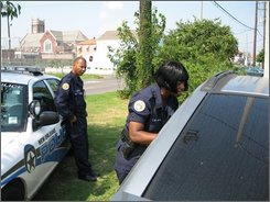 "New Orleans Police Officer John Blatcher., left, looks on as partner Carolyn Dalton tries to convince a teen she needs to evacuate the city with her mother ahead of Hurricane Gustav on Saturday, Aug. 30, 2008 in New Orleans. Dalton, who stood by her post during Katrina, took her two sons to her mother's house in the days leading up to that storm. This past weekend, she made the journey again, leaving 15-year-old son Lace with a hug and some money, then returning to New Orleans for her 7 a.m. shift. Blatcher's wife and children left for Atlanta on Saturday. ""We try to learn the lessons of the past,"" he said. ""I think the city of New Orleans has learned the lessons of Katrina."" (AP Photo/Allen G. Breed)"