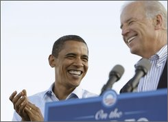 Democratic presidential candidate, Sen. Barack Obama, D-Ill., left, smiles as his vice presidential running mate, Sen. Joe Biden, D-Del., speaks at a rally at Dublin Coffman High School football stadium in Dublin, Ohio Saturday, Aug. 30, 2008.(AP Photo/Alex Brandon)