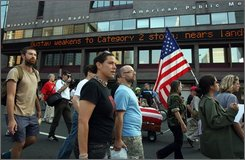 Protesters walk with members of the group Iraq Veterans Against the War, past a ticker that mentions Hurricane Gustav at the Republican National Convention in St. Paul, Minn., Monday, Sept. 1, 2008.  The veterans group decided to go ahead with a planned protest as news of the Hurricane continued to come in. (AP Photo/Ross D. Franklin)