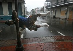 New Orleans residents Roberto Yuill makes light of the situation by pretending the wind is blowing him away in front of Johnny Whites in the French Quarter as Hurricane Gustav enters the area on Monday, Sept. 1, 2008, in New Orleans. (AP Photo/Houston Chronicle, Mayra Beltran)