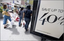 Shoppers on New York's 34th Street pass a 40% off sales sign in front of a Banana Republic store, Friday afternoon Aug. 29, 2008. In a bid to pull in frugal shoppers into their stores, the nation's retailers are slashing their prices on everything from jeans to home appliances. But those 50 percent discounts on jeans and the 60 percent reductions on dinnerware will likely come at a big price for retailers.  (AP Photo/Richard Drew)
