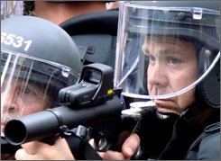 A police officer raises his weapon during a protest at the Republican National Convention in St. Paul, Minn., Tuesday, Sept. 2, 2008.  (AP Photo/Kathryn Grim)