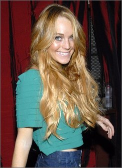 In this Aug. 14, 2008 file photo, actress Lindsay Lohan poses on the press line at the Apple Lounge grand opening in West Hollywood, Calif. (AP Photo/Dan Steinberg, file)