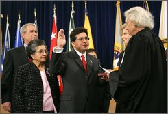 In this Feb. 14, 2005 file photo, Attorney General Alberto Gonzales is sworn in by Supreme Court Justice Sandra Day O'Connor, right, during a ceremony at the Justice Department in Washington, with President Bush, left, his mother Maria Gonzales, second from left, and his wife Rebecca, second from left. Former Attorney General Alberto Gonzales mishandled highly classified notes about a secret counterterror program, but not on purpose, according to a memo by his legal team. (AP Photo/Susan Walsh, file)