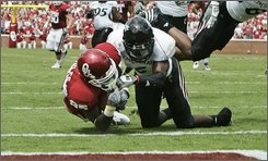 Oklahoma wide receiver Ryan Broyles, left, dives into the end zone with a touchdown as Cincinnati defender DeAngelo Smith, right, attempts a tackle, in the first quarter of an NCAA college football game in Norman, Okla., Saturday, Sept. 6, 2008.  (AP Photo/Sue Ogrocki)