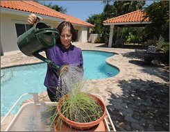 Suzanne Bonner waters potted herbs in back of her Palmetto Bay, Fla., home Saturday, Sept. 6, 2008. Bonner, whose home was ravaged during Hurricane Andrew in 1992 and damaged in Hurricane Wilma in 2005, says she rises at 5 a.m. each day to watch the tropical weather update on the Weather Channel and spend much time perusing meteorological internet portals for the latest information regarding tropical cyclones. (AP Photo/Andy Newman)
