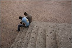 Two men who did not want to be identified sit on the stairs outside a police station after one of their friends was detained in Mexico City, Sunday, July 13, 2008. Under the constitutional amendment passed by the legislature, approved by country's 32 states and signed by President Felipe Calderon, Mexico has eight years to replace its closed proceedings with public oral trials in which suspects are presumed innocent, legal authorities can be held more accountable and equal justice is promised to all. (AP Photo/Dario Lopez-Mills)