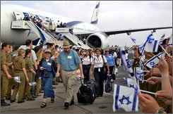 In this Aug. 4, 2004 file photo a family of new immigrants from North America walks as they arrive to Israel at Ben Gurion airport near Tel Aviv,Since its creation in 1948, Israel has brought more than 3 million Jewish immigrants from more than 100 countries. Israel's appeal to the Jewish Diaspora used to be as a small feisty nation fighting for its survival, or as a socialist alternative to the capitalist rat race. There were kibbutzim to farm and deserts to make bloom. But today the Jewish state is in many ways a normal industrialized democracy. Its immigrants today are as likely to be job-hunting non-Jews from Africa and Asia, many of them here illegally, as Zionists in search of spiritual fulfillment.(AP Photo/Ariel Schalit, File)