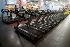 People are shown exercising on running machines at a fitness club in Beijing, China, Wednesday, Sept. 3, 2008. (AP Photo/Alexander F. Yuan)