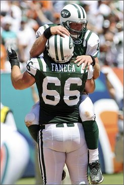 New York Jets quarterback Brett Favre, rear, celebrates with Alan Faneca after the Jet's second touch down in the second quarter of a football game against the Miami Dolphins Sunday, Sept. 7, 2008 at Dolphin Stadium in Miami. (AP Photo/Jeffrey M. Boan)
