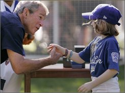 President Bush, left, congratulates 8-year-old Bridget Donahue of Westborough, Mass., the daughter of Coast Guard Chief Petty Officer William Donahue, following a Tee Ball on the South Lawn baseball game, Sunday, Sept. 7, 2008, at the White House in Washington. The game, the 20th of the administration, is scheduled to be the last game Bush will host before leaving office. (AP Photo/Haraz N. Ghanbari)