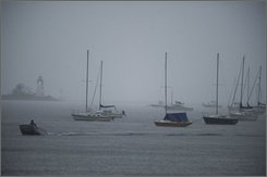 A lone boatman heads into a protective cove in Bridgport, Conn. Saturday, Sept. 5, 2008 as sailboats are secured for Tropical Storm Hanna. (AP Photo/Douglas Healey)