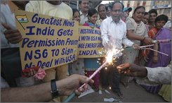 People hold placards and burn firecrackers to celebrate Saturday?s developments in the India-US nuclear deal, in Ahmadabad, India, Saturday, Sept. 6, 2008. Nations that supply nuclear material and technology overcame fierce obstacles Saturday and approved a landmark U.S. plan to engage in atomic trade with India, a deal that reverses more than three decades of American policy. (AP Photo/Ajit Solanki)
