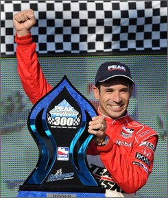 Helio Castroneves, of Brazil, celebrates after winning the IndyCar Series' PEK Indy 300 auto race at Chicagoland Speedway in Joliet, Ill., Sunday, Sept. 7, 2008. (AP Photo/Paul Beaty)
