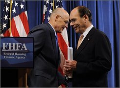 Treasury Secretary Henry Paulson, Jr., left, and Federal Housing Finance Agency Director James Lockhart, right, exchanges places during their news conference in Washington, Sunday, Sept. 7, 2008 on the bailout of mortgage giants Fannie Mae and Freddie Mac. (AP Photo/Susan Walsh)