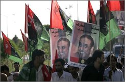 Supporters of the Pakistan People's Party cheer in the street with posters of President-elect Asif Ali Zardari during a rally in Islamabad,   Pakistan, Monday, Sept. 8, 2008. Zardari, widower of slain former premier Benazir Bhutto became Pakistan's new president Saturday after winning a landslide election victory that makes him a critical partner of the West against international terrorism. (AP Photo/Wally Santana)