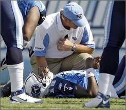 Tennessee Titans quarterback Vince Young is attended to by a trainer after being injured while playing the Jacksonville Jaguars in the fourth quarter of an NFL football game in Nashville, Tenn., Sunday, Sept. 7, 2008. The Titans won 17-10. (AP Photo/Mark Humphrey)
