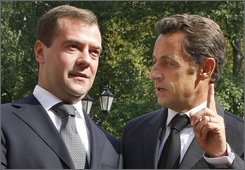 Russian President dmitry Medvedev, left, listens to French President Nicolas Sarkozy, at the presidential residence, outside Moscow, Monday, Sept. 8, 2008. French President Nicolas Sarkozy, European Commission President Jose Manuel Barroso and EU foreign policy chief Javier Solana began the difficult mission on Monday of trying to persuade Russia to honor its pledge to withdraw troops from Georgia. (AP Photo/RIA Novosti, Dmitry Astakhov, Presidential Press Service)