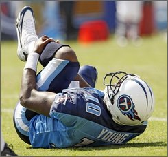 Tennessee Titans quarterback Vince Young rolls on the ground after spraining his knee in the fourth quarter of an NFL football game against the Jacksonville Jaguars in Nashville, Tenn., Sunday, Sept. 7, 2008. The Titans won 17-10 but Young left the game and is questionable for Sunday's game against Cincinnati. (AP Photo/John Russell)