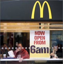 In this Jan. 28, 2008 file photo, the front window of a branch of McDonald's is seen in London. Overseas consumers spent more at McDonald's Corp. in August than Wall Street expected, leading the nation's No. 1 hamburger chain to surprise investors by posting a big rise in global same-store sales on Tuesday. (AP Photo/Matt Dunham, file)