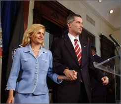 In this Thursday, Aug. 12, 2004 picture, New Jersey Gov. James E. McGreevey, right, holds his wife Dina Matos McGreevey's hand, before announcing he will resign, during a news conference at the Statehouse in Trenton, N.J. The ex-wife of former New Jersey Gov. Jim McGreevey said Wednesday, Sept. 10, 2008 she has decided to drop a fraud claim against him, bringing finality to a protracted, bitter and very public parting set in motion four years ago when McGreevey announced he is gay. (AP Photo/Brian Branch-Price)
