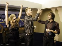 Hillary Scott, left, Charles Kelley, center, and Dave Haywood, right, of the country music group Lady Antebellum, celebrate upon hearing they are one of the Country Music Association awards nominees for vocal group of the year that were announced in New York, Wednesday, Sept. 10, 2008, in Nashville, Tenn. (AP Photo/Mark Humphrey)