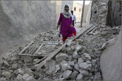 Iranian villagers walk through ruins after an earthquake at the Zeynabi village in the Iranian Qeshm Island in the Persian Gulf, Wednesday, Sept. 10, 2008. A strong earthquake rocked southern Iran on Wednesday, sending tremors across the Persian Gulf and shaking the skyscrapers of Dubai. Iranian state television reported that five people were killed and 26 others were injured. (AP Photo/Abdolhosein Rezvani)