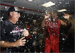 Los Angeles Angels manager Mike Scioscia, left, celebrates with Torii Hunter after the Texas Rangers lost to Seattle Mariners following the Angels victory over the New York Yankees, allowing the Angels to clinch the American League West title in Anaheim, Calif., Wednesday Sept.. 10, 2008. (AP Photo/Kevork Djansezian)