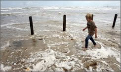 Dawson Voris, 9, of Corpus Christi, Texas, walks through storm surge water from Hurricane Ike as the water pushes over the Padre Balli Park beach in Padre Island, Texas, and into the parking lot Thursday, Sept. 11, 2008. (AP Photo/Corpus Christi Caller-Times,Todd Yates)