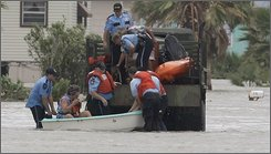 Surfside police and firefighters help evacuate David and Dondi Fields with the a kayak and large truck as Hurricane Ike causes flood waters in their neighborhood, in Surfside  Beach, Texas, Friday, Sept. 12, 2008. A massive Hurricane Ike sent white waves crashing over a seawall and tossed a disabled 584-foot freighter in rough water as it steamed toward Texas Friday, threatening to devastate coastal towns and batter America's fourth-largest city. (AP Photo/Eric Gay)