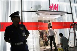 A security officer stands guard in front of  H&M's first Japan store in Tokyo's Ginza shopping district Wednesday, Sept. 10, 2008 as workers give a finishing touch at the main entrance prior to its Saturday opening. H&M is arriving in Japan, seeking to woo a nation of notoriously finicky luxury-lovers with the same cheap prices that have made the Swedish fashion retailer a hit in the U.S. and Europe. (AP Photo/Shizuo Kambayashi)
