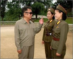 In this Korean Central News Agency's undated photo released Aug. 14, 2008 by Korea News Service in Tokyo, North Korea's leader Kim Jong Il, left, inspects women troop at an undisclosed place in North Korea. Speculation that Kim Jong Il may have become ill intensified after he missed a parade Tuesday, Sept. 9, 2008 commemorating the communist state's founding 60 years ago. Kim has been absent from public view since mid-August. (AP Photo/Korean Central News Agency via Korea News Service)