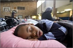 Next to nearly 40 others evacuees, Zaylan Shaffer, 4, sleeps on a cot in the Killeen Community Center in Killeen, Texas, on Thursday afternoon, Sept. 11, 2008. Shaffer, from Ontario, Canada, was on vacation with his family in Bay City, Texas, when residents were asked to evacuate the area. Precautions for Hurricane Ike has displaced evacuees all over Central Texas with Killeen at over 100 evacuees so far and numbers are expected to increase by the weekend.  (AP Photo/Killeen Daily Herald, Sarah Moore Kuschell)