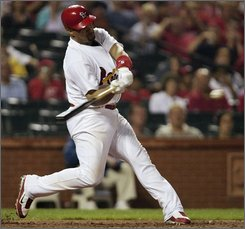 St. Louis Cardinals' Albert Pujols swings for an RBI double in the sixth inning against the Chicago Cubs in a baseball game Thursday, Sept. 11, 2008, in St. Louis. The RBI was Pujols' 100th of the season. (AP Photo/Tom Gannam)