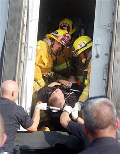 Los Angeles firefighters hand a victim from train car to waiting Los Angeles Police officers at the scene of a train accident in Los Angeles, Friday, Sept. 12, 2008. A Metrolink commuter train believed to be carrying up to 350 people collided with a freight train Friday, killing four people and injuring dozens of others. (AP Photo/Mike Meadows)